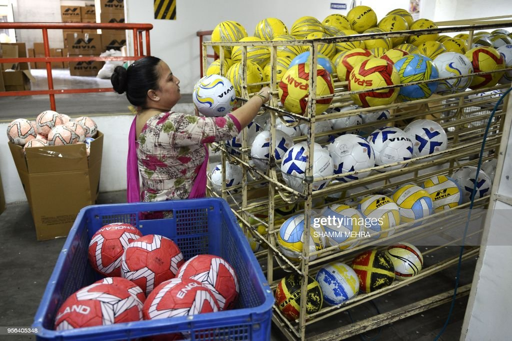 An Indian worker stores football ahead of the Russia 2018 FIFA World Cup at a manufacturing unit in Jalandhar on May 9 2018