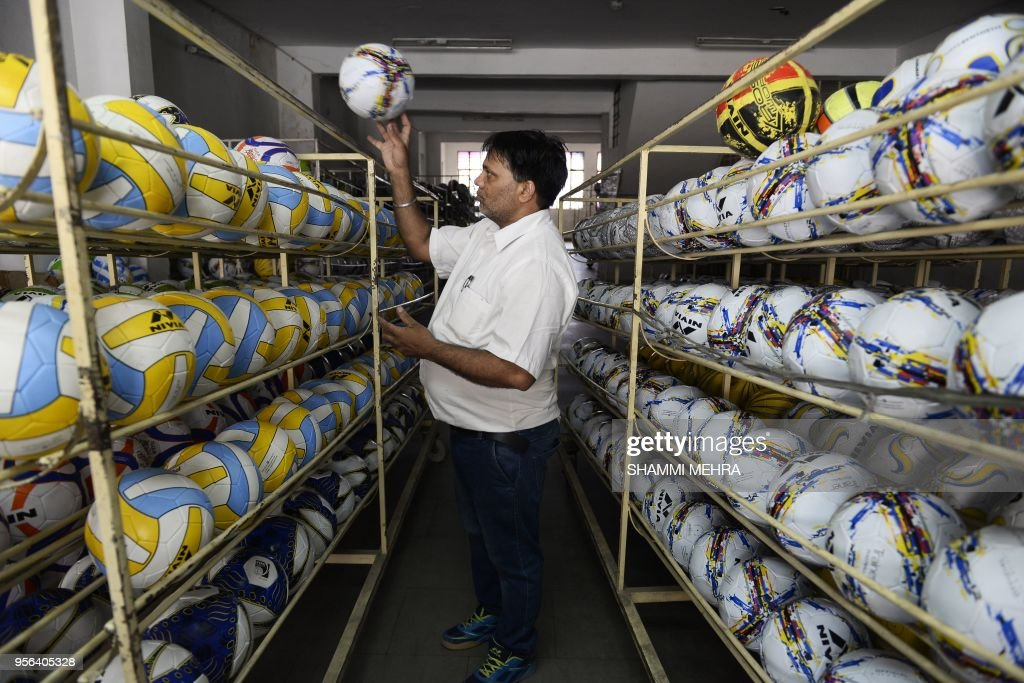 An Indian worker stores footballs ahead of the Russia 2018 FIFA World Cup at a manufacturing unit in Jalandhar on May 9 2018