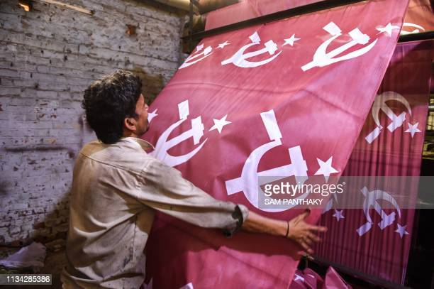 An Indian worker supervises the printing process of textile materials dedicated to the Communist Party of India ahead of India's general election on...