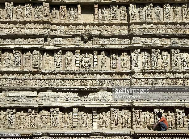 An Indian worker sweeps the carved walls of The Ran Ki Vav Stepwell at Patan some 120kms from Ahmedabad on November 21 2008 The Archaeological Survey...