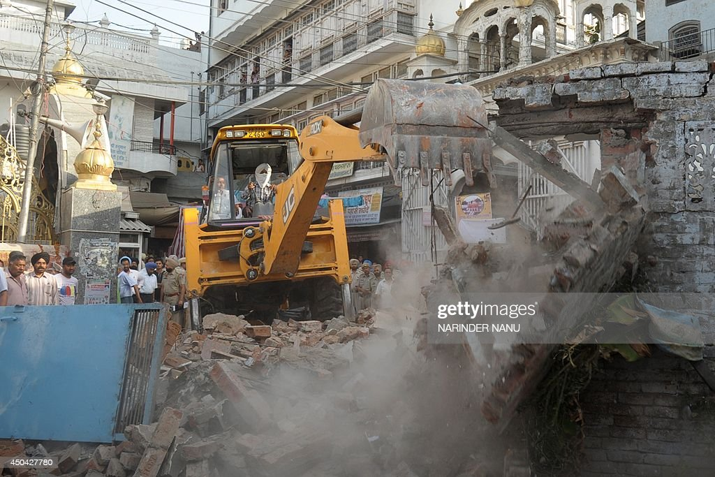An Indian worker uses an excavator to demolish shops and houses near the historical Durgiana Temple complex in Amritsar on June 11 2014 Some 37...