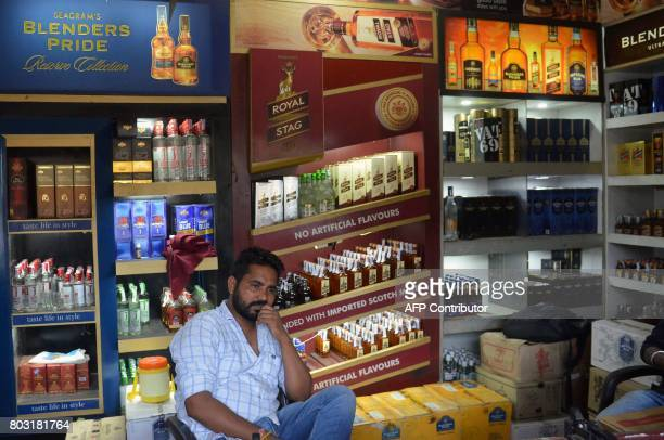 An Indian worker waits for customer at a liquor shop in Amritsar on June 29 2017 India is bracing for its most significant reform in a generation as...