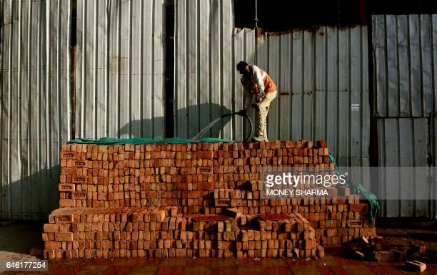 An Indian worker waters a stack of bricks at a construction site in New Delhi on February 28 2017 India's economic growth rate fell to seven percent...