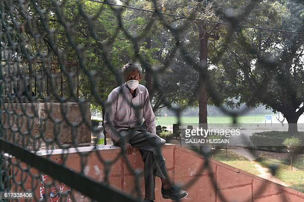 An Indian worker wears a mask as he sits inside the entry gate of the Deer Park which is temporarily closed for visitors as a precautionary measure...