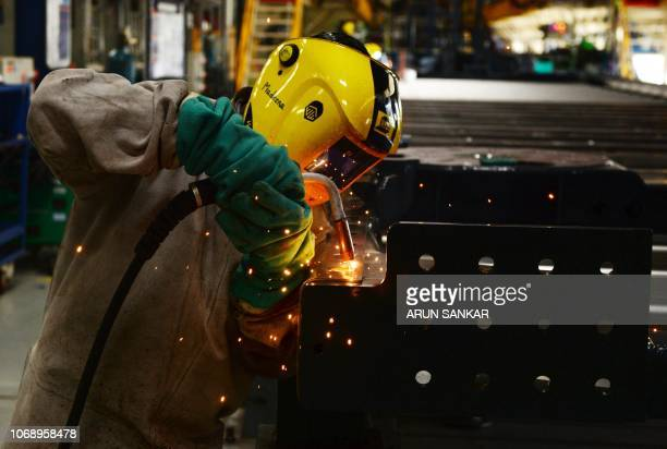 An Indian worker welds a frame at Alstom's metro rail construction facility in Sri City some 55 km north of Chennai on December 6 2018 Alstom...