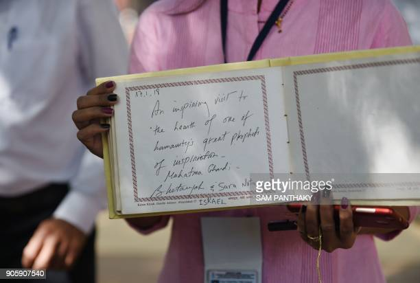 An Indian workers holds the guest book signed by Israeli Prime Minister Benjamin Netanyahu and his wife Sara Netanyahu wave during a visit to the...