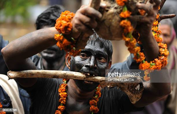 An Indian worshipper of Hindu God Lord Shiva holds human skulls and bones as he takes part in a religious procession to mark the Hindu festival of...