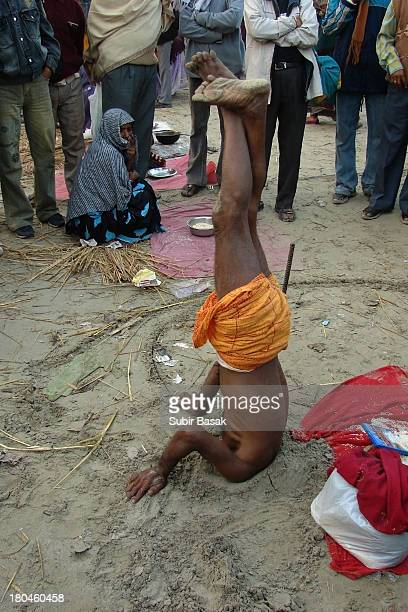 An Indian yogi showing yoga by put his head below the ground on January 14,2009 at Gangasagar islands,West bengal,India. Sadhus and Hindu piligrims...