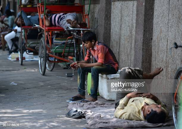 An Indian young boy uses his cellphone as other take nap along a roadside during a hot summer day in the old quarters of New Delhi on April 26 2018