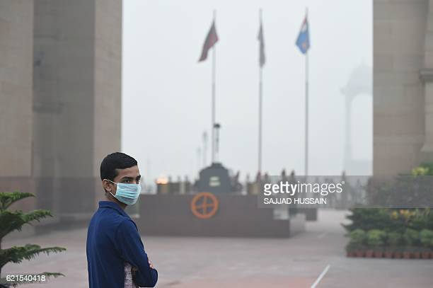 An Indian youngster wears a mask as he stands at the India Gate monument whilst heavy smog covers New Delhi on November 7 2016 Schools in the Indian...
