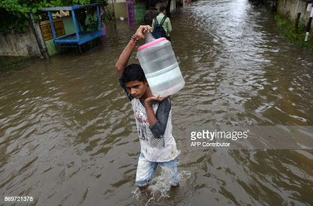 An Indian youth carries a container of drinking water on his shoulders at a residential area flooded after heavy monsoon rains in Chennai on November...