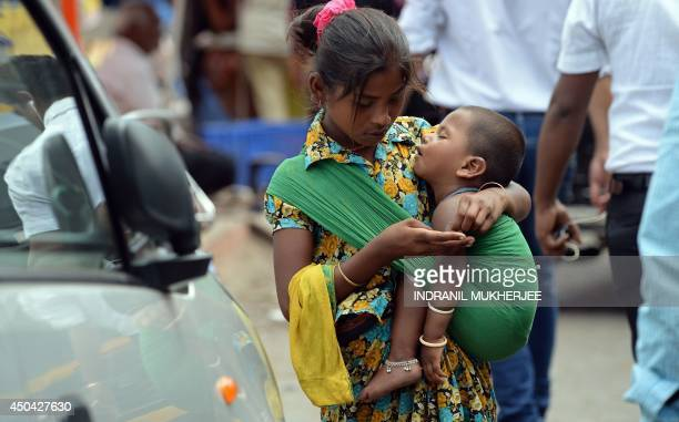 An Indian youth carrying a toddler counts money collected by begging from commuters at a busy traffic intersection on the eve of World Day Against...