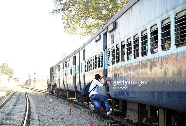 An indian youth catches a moving train at Daraganj Railway stationas Union Railway minister Mr Suresh Prabhu announces rail budget 2016 in Allahabad...
