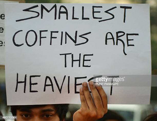 An Indian youth holds a placard during a vigil in Mumbai on December 22 held for schoolchildren and teachers killed in an attack by Taliban militants...