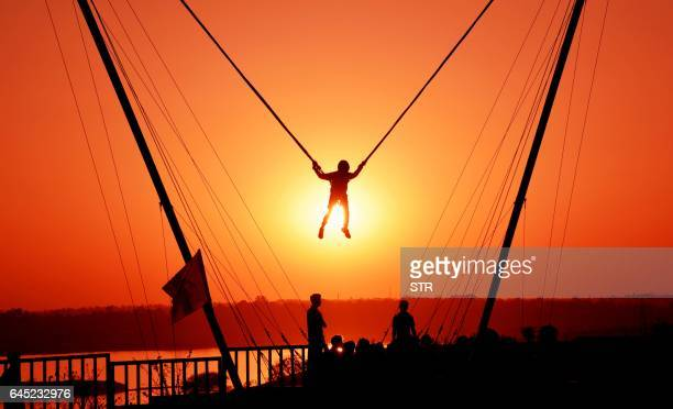 TOPSHOT An Indian youth is watched by others as he takes part in a 'bunjee jumping' activity at sunset during the 'Bhoj Adventure Festival 2017' in...