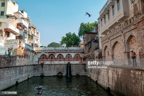 An Indian youth jumps from the top of a building while others cool off at the Hazrat Nizamuddin Ki Baoli during a hot summer day in New Delhi on June...
