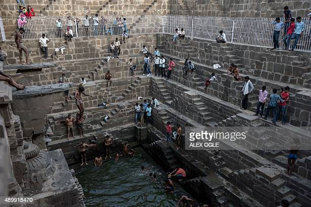 An Indian youth jumps into the historic Chand Baori stepwell as others look on in Abhaneri village in Rajasthan on September 24 2015 For a few hours...