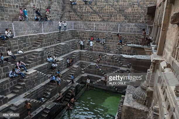 An Indian youth jumps into the water of the historic Chand Baori stepwell as others look on in Abhaneri village of western Rajasthan state on...