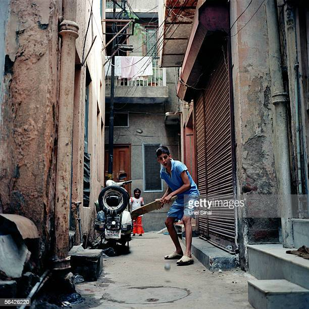 An Indian youth plays cricket in a rundown street September 26 2005 in New Delhi India Although India occupies only 24% of the world's land area it...