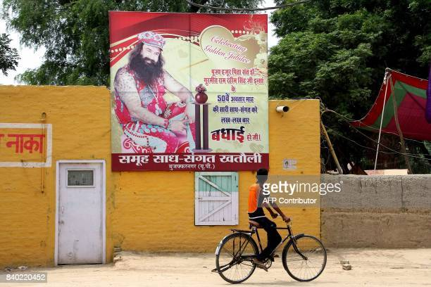 An Indian youth rides a bicycle past a poster of controversial guru Gurmeet Ram Rahim Singh in Sirsa on August 28 2017 An Indian court sentenced a...