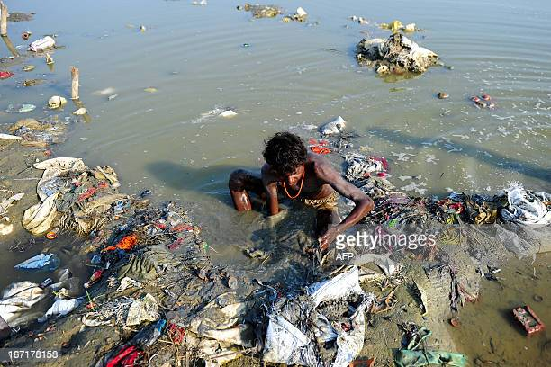 An Indian youth searches through mud for coins and other items of value in the polluted banks of the River Ganges at Sangam in Allahabad during World...