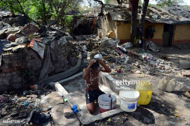 An indian youth takes bath near a drinking water tap in a slum area on World Water Day in the outskirts of Allahabad on march 222017 One in four of...