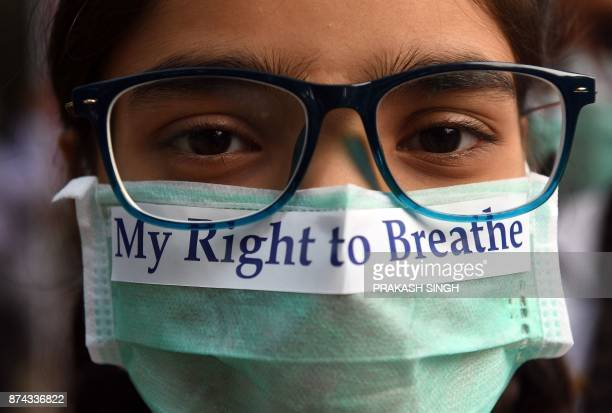 TOPSHOT An Indian youth wearing a pollution mask participates in a march to raise awareness of air pollution levels in New Delhi on November 15 2017...