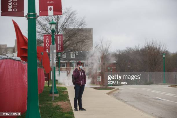 An Indiana University student, who said he's an international student, and stuck in the United States, waits for a bus near the university. Student...