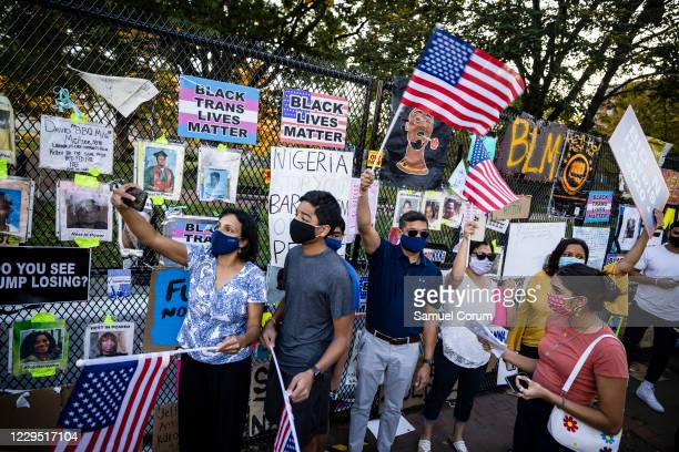 An Indian-American family waves American flags as thousands gather at Black Lives Matter Plaza near the White House to celebrate the announcement...