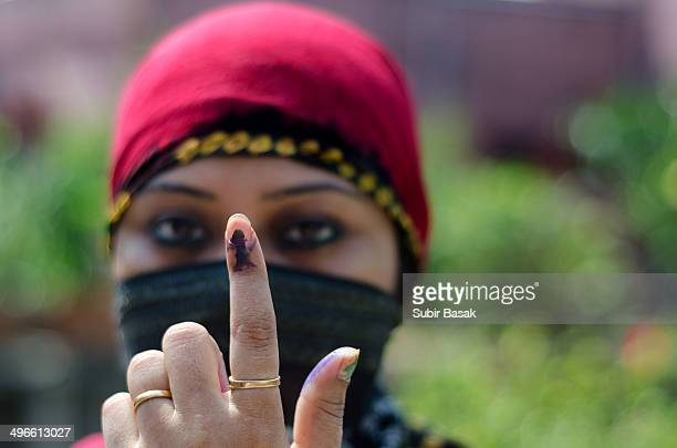 An Indianwoman voter displays his inked finger .