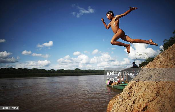 An indigenous boy jumps while bathing in the Madre de Dios River in the Amazon lowlands on November 14 2013 in the indegenous community of Palma Real...