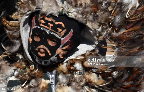 An indigenous boy wearing a costume made of hen feathers participates in a tribute to the patron saint of the indigenous people San Francisco Solano...