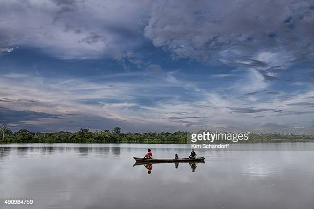 An indigenous Family sailing on a lake in the Amazon jungle in their canoe