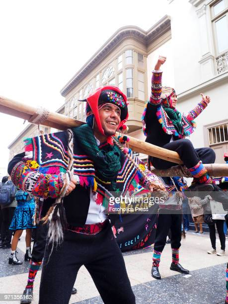 An indigenous man in traditional dress carrying another one in a litter during the grand parade in the downtown of Lima for the 69th anniversary of...