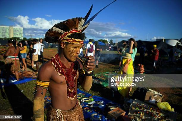 An indigenous man smokes a pipe at a protest camp in Brasilia on April 25 2019 Thousands of indigenous people decorated with traditional feathers and...
