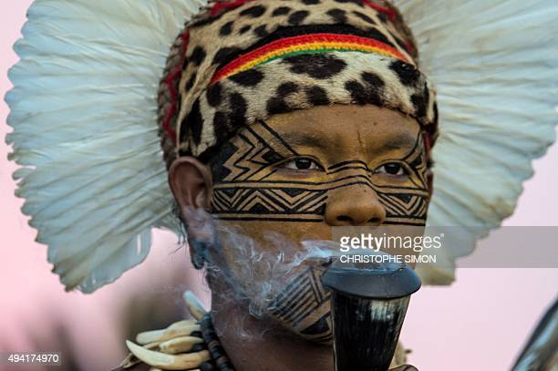 An indigenous man smokes a pipe during the I World Indigenous Games in Palmas Tocantins on October 24 2015 AFP PHOTO / CHRISTOPHE SIMON