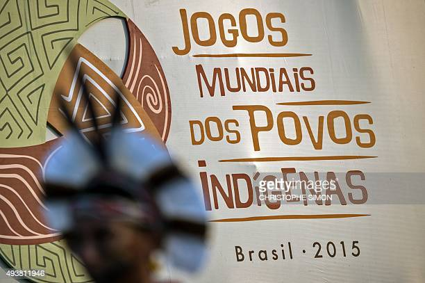 An indigenous man stands in front of the sign of the first World Indigenous Games in Palmas Tocantins Brazil on October 22 on the eve of its...