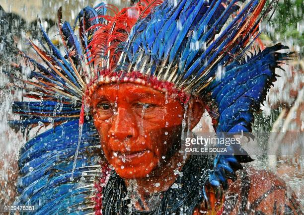 An Indigenous man stands under a water fountain outside a government building in Brasilia on April 26 during the last day of a protest camp...