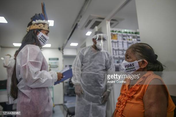An Indigenous nurse wearing a protective mask helps an elderly woman to make testing at the Parque das Tribos community on May 21 2020 in Manaus...