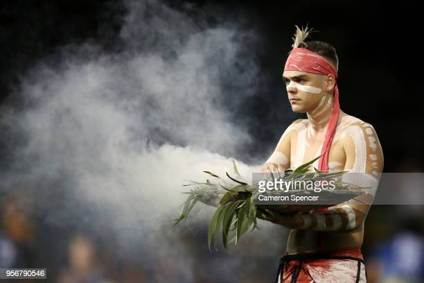 An Indigenous performer participates in a smoking ceremony as part of the Indigenous round during the round 10 NRL match between the Wests Tigers and...