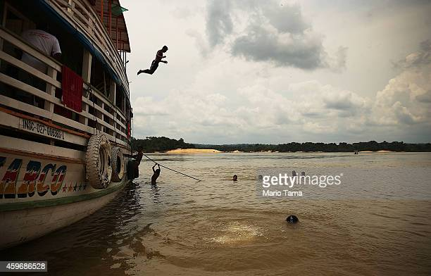 An indigenous tribe member leaps off a riverboat as others swim in the Tapajos River during a 'Caravan of Resistance'' protest by indigenous groups...