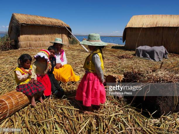 An indigenous Uro family sitting on their own floating island of Totora on Titicaca lake The Uru or Uros are indigenous people of Peru and Bolivia...