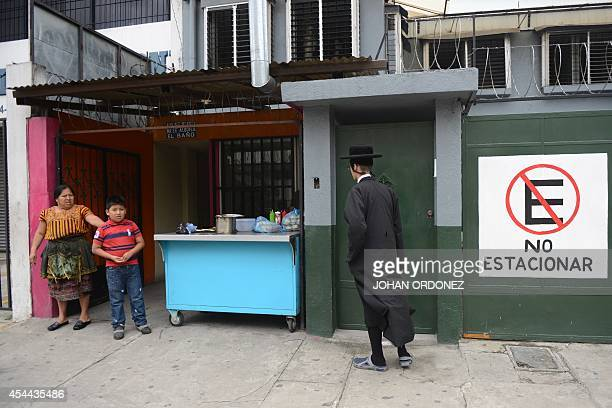 An indigenous woman and her son look at a member of an ultraOrthodox Jewish group outside the building where the community stays in Guatemala City on...