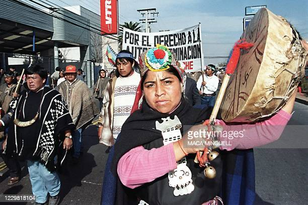 An indigenous woman holds a drum as she marches 20 June 1999 in Santiago to protest govenment policies towards indigenous people. Una mujer indigena...