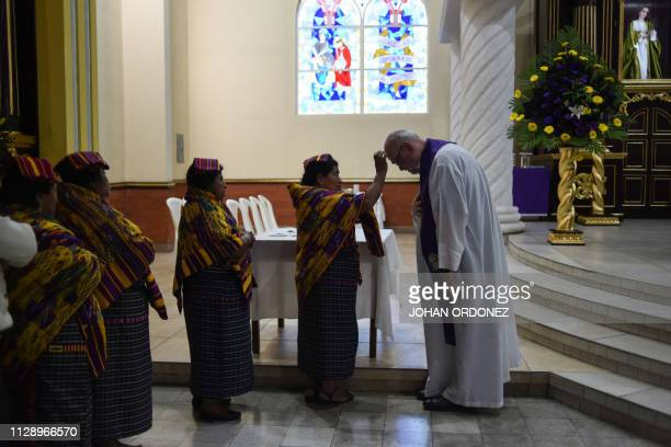 An indigenous woman marks the symbol of the cross with ash on a priest's forehead during the celebration of Ash Wednesday at San Juan Sacatepequez's...