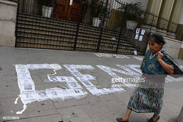 An indigenous woman passes by the word 'Genocide' formed with pictures of missing people on the sidewalk outside the presidential residence during a...