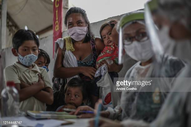 An indigenous woman wearing a protective mask holds her kids while waiting for vaccination at Parque das Tribos community on May 21 2020 in Manaus...