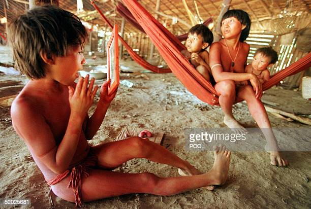 An indigenous Yanomami boy looks into a mirror beside other Yanomami youths on a hammock 22 March in Demini as huge fires in the rain forest of...
