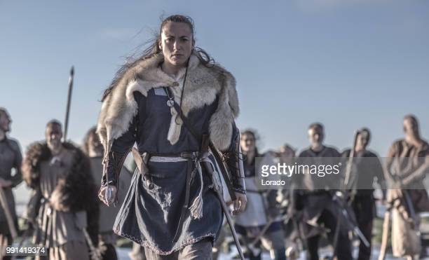 an individual female viking posing in front of a group of warriors stood in the surf on the shore - medieval stock pictures, royalty-free photos & images