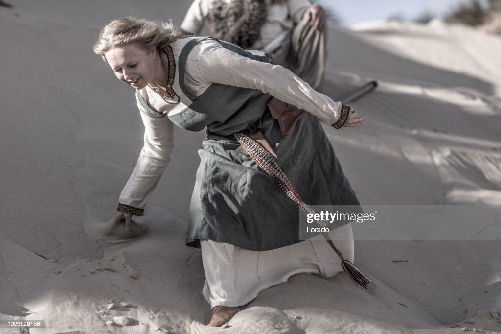 An individual female viking warrior in action on a sandy battlefield dune : Stock Photo